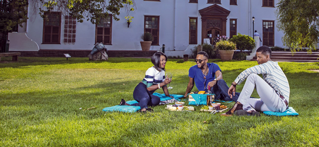 Three adults smile while having a picnic on a lush lawn in Bloemfontein, which can be experienced when you book your hotel or other accommodation with Flight Centre.