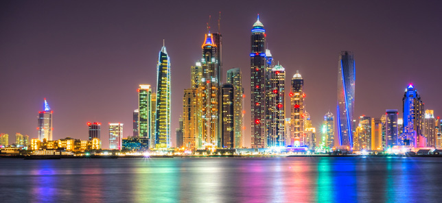 A view of Dubai at night, which can be visited when you book a hotel or other accommodation with Flight Centre.
