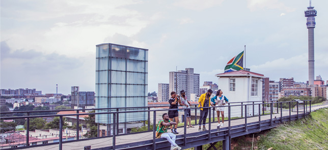 A crowd of people lean against the rails of a bridge in Johannesburg, where you can book hotels and other accommodation with Flight Centre.