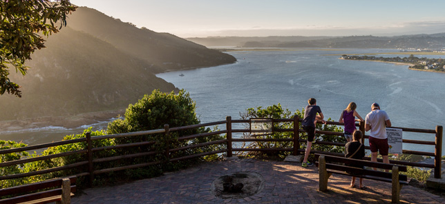 Several people watch across some of Knysna's coast, which can be experienced when you book a hotel or other accommodation in Knysna with Flight Centre.