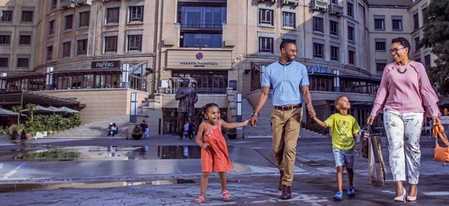A family smile while walking through Nelson Mandela Square in Sandton, which can be visited when you book your hotel or other accommodation with Flight Centre.