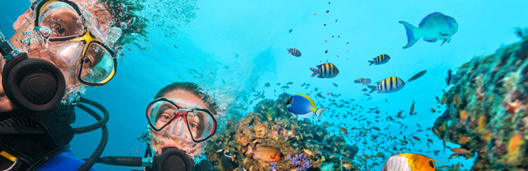 A couple scuba dive in the Maldives, which can be visited with a holiday package from Flight Centre.