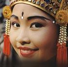 A woman in traditional clothing in Bali, which can be seen via a cheap flight from Flight Centre.