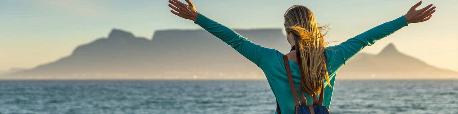 A woman stands with her arms stretched on the beach with a view of Table Mountain in Cape Town, which can be visited with a cheap holiday package from Flight Centre.