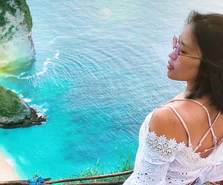 A woman looks across the sea on her Bali holiday, which she took via a cheap Bali Holiday package from Flight Centre.