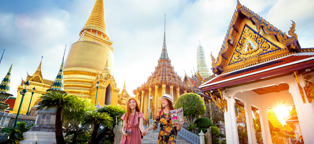 A view of two women smiling in front temple in Thailand, which can be visited when you book a hotel or other accommodation with Flight Centre.