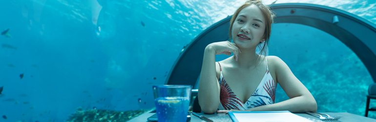 A woman sits at a table at an underwater restaurant in the Maldives, which can be visited with a holiday package from Flight Centre.